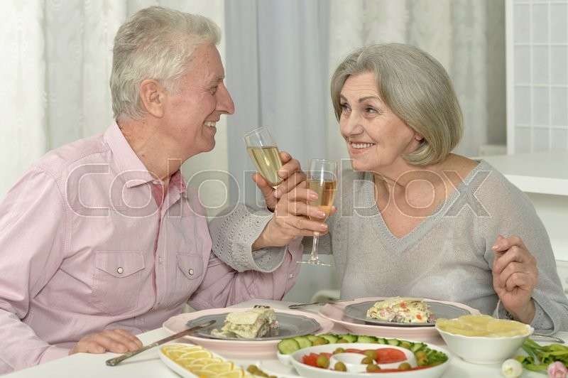 Stock image of 'Portrait of a happy senior couple resting at cafe'