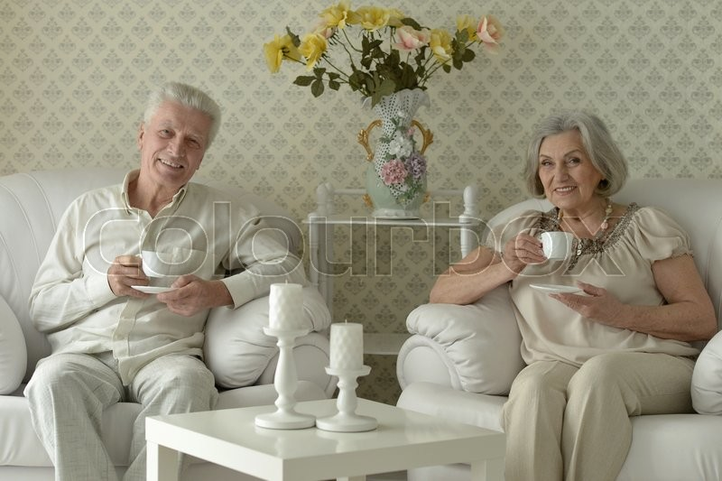 Stock image of 'happy Senior couple resting at home with tea cups'
