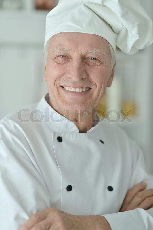 Stock image of 'Portrait of a happy elderly male chef'