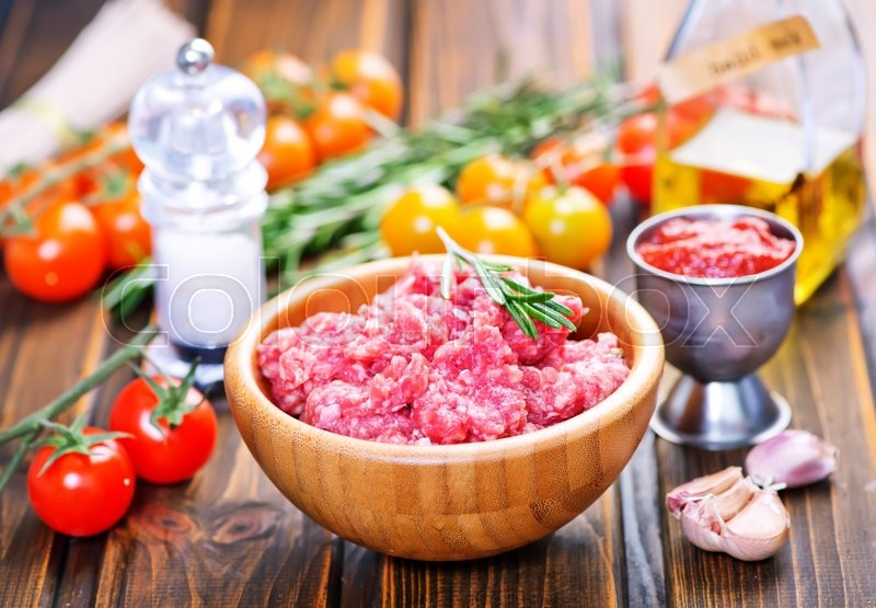 Stock image of 'raw minced meat in bowl and on a table'