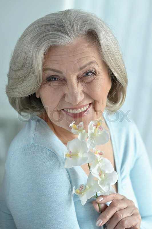 Stock image of 'Senior woman portrait with blooming orchid flowers'
