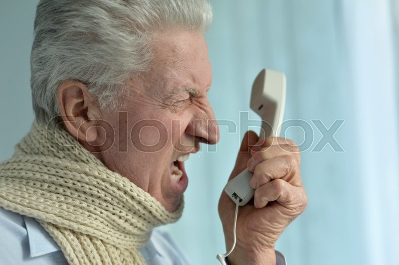 Stock image of 'Portrait of an angry senior man with phone'