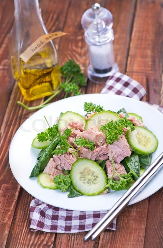 Stock image of 'salad with tuna on plate and on a table'