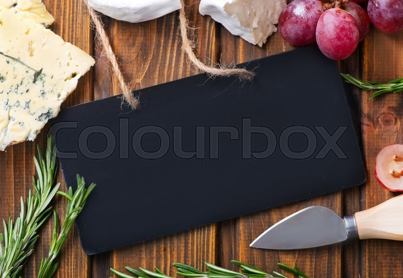 Stock image of 'cheese and grape on the wooden table'