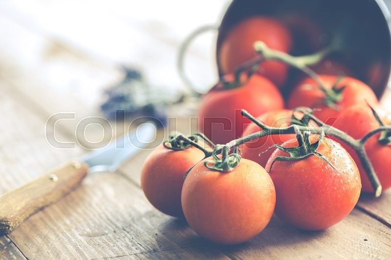 Stock image of 'Fresh ripe tomatoes spread by a window'