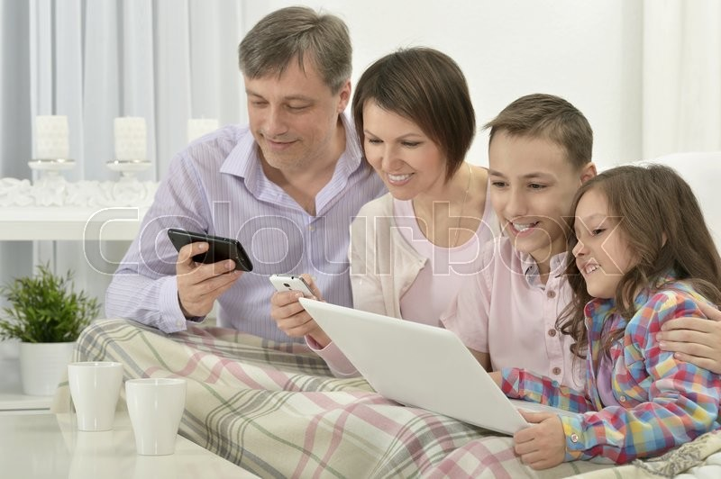 Stock image of 'Happy family with laptop in a room'