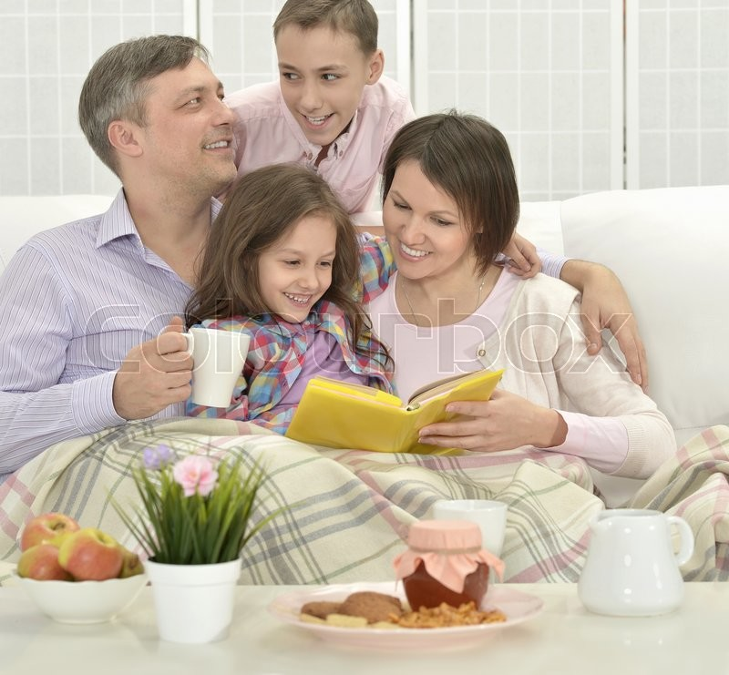 Stock image of 'Happy family  in a room reading book'