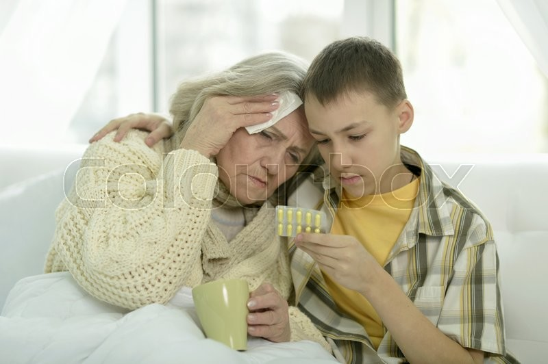 Stock image of 'Portrait of sick  senior woman with her grandson in bed'