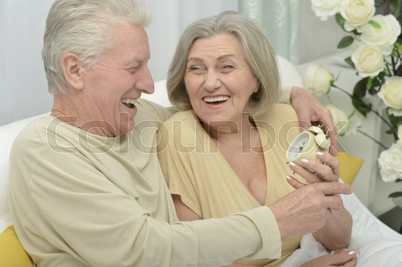 Stock image of 'Senior couple portrait in bed with alarm clock'
