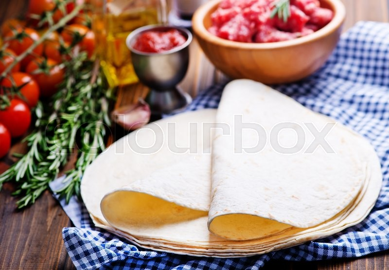 Stock image of 'Ingredients for tacos, meat and taco on a table'