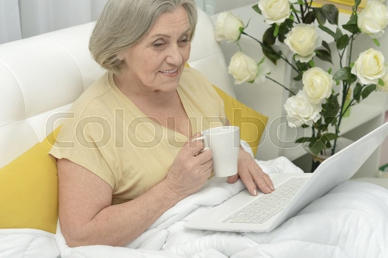 Stock image of 'Senior woman portrait in bed with laptop'