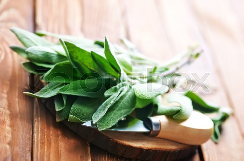 Stock image of 'fresh sage on the wooden board and on a table'