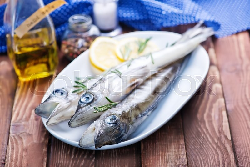 Stock image of 'raw fish with salt and lemon on a table'