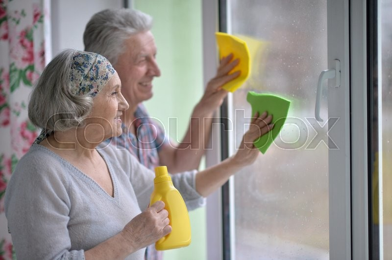 Stock image of 'happy Senior couple cleaning window at home'