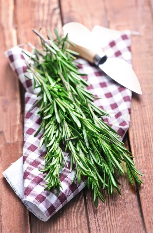 Stock image of 'green rosemary with knife on a table'