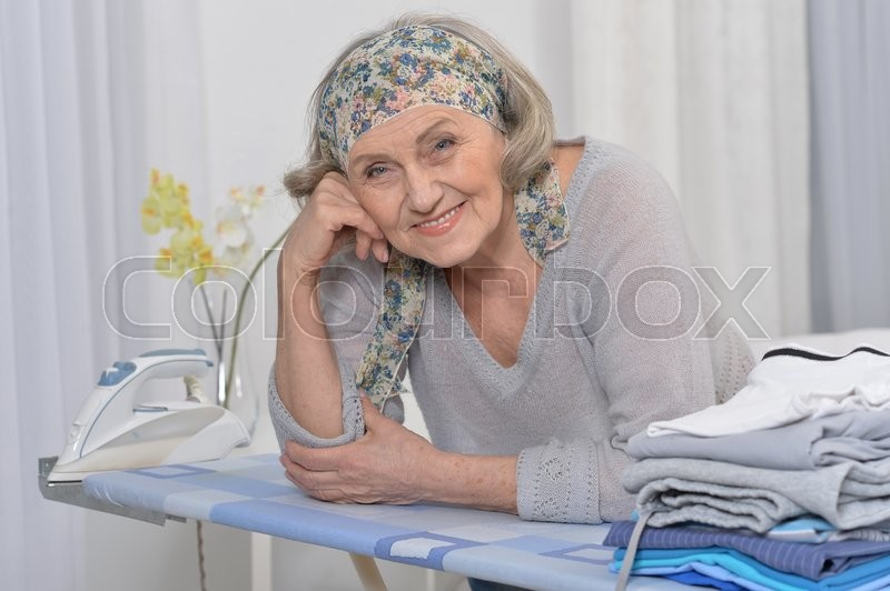 Stock image of 'Portrait of a senior woman  during ironing'