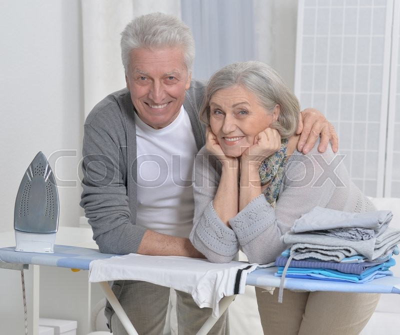 Stock image of 'happy Senior couple during ironing at home'