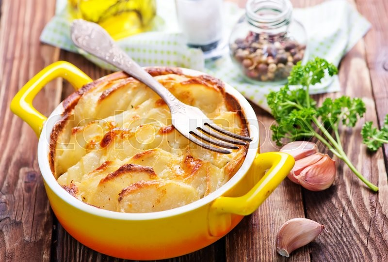 Stock image of 'baked potato in bowl and on a table'