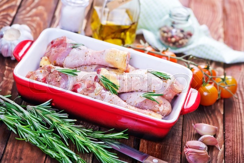 Stock image of 'raw chicken legs in bowl with spice and salt'