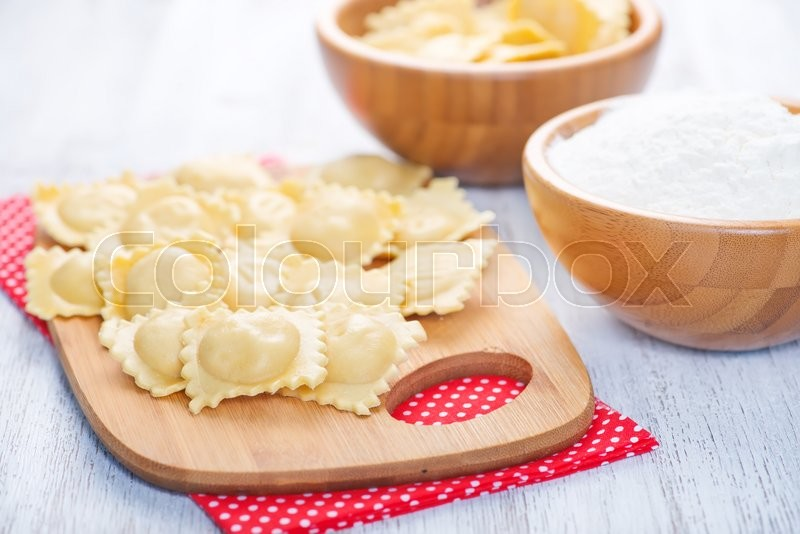 Stock image of 'raw ravioli and flour in the bowl and on a table'