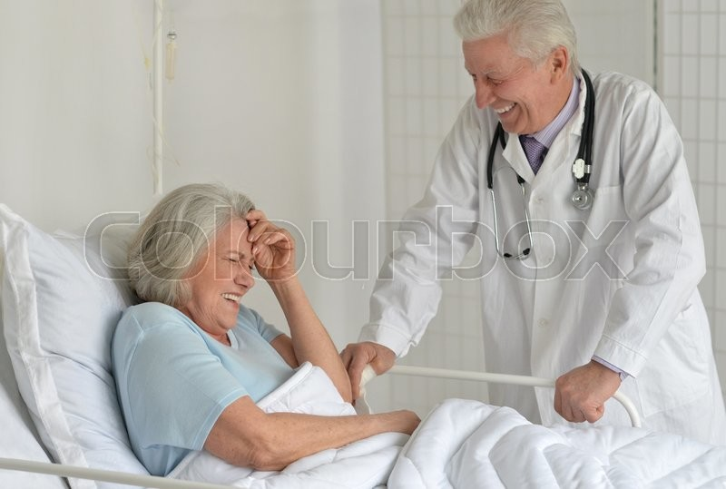 Stock image of 'happy Senior woman in hospital with caring doctor'
