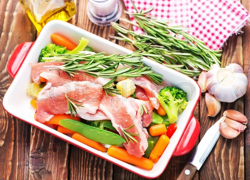 Stock image of 'raw meat with vegetables in bowl and on a table'