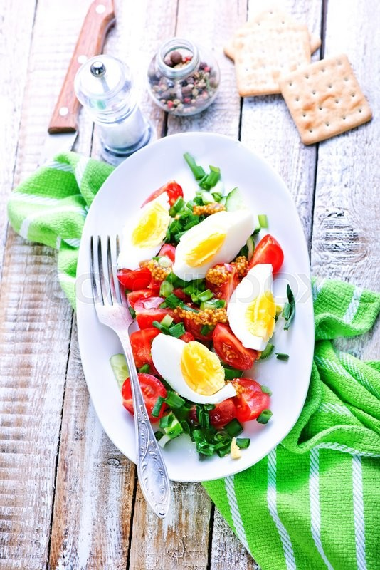 Stock image of 'salad with egg on plate and on a table'