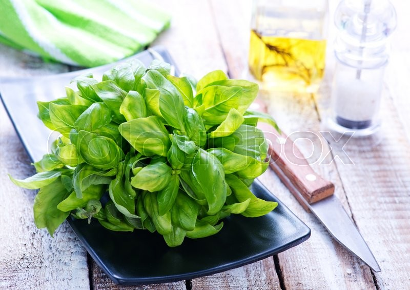 Stock image of 'fresh basil on black plate and on a table'