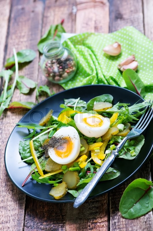 Stock image of 'salad with eggs on plate and on a table'