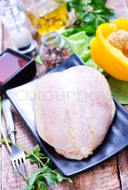 Stock image of 'chicken fillet on plate and on a table'