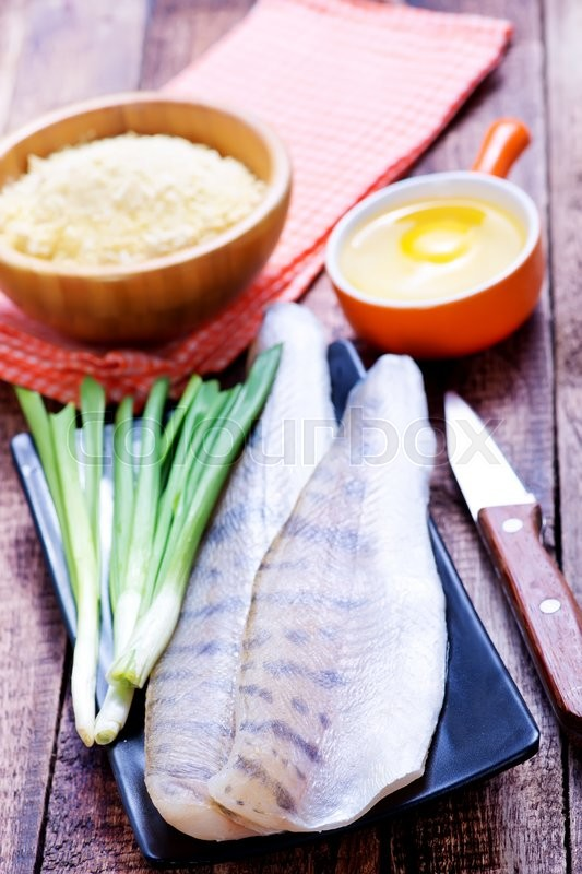 Stock image of 'raw fish on plate and on a table'