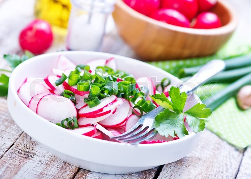 Stock image of 'radish salad in bowl and on a table'