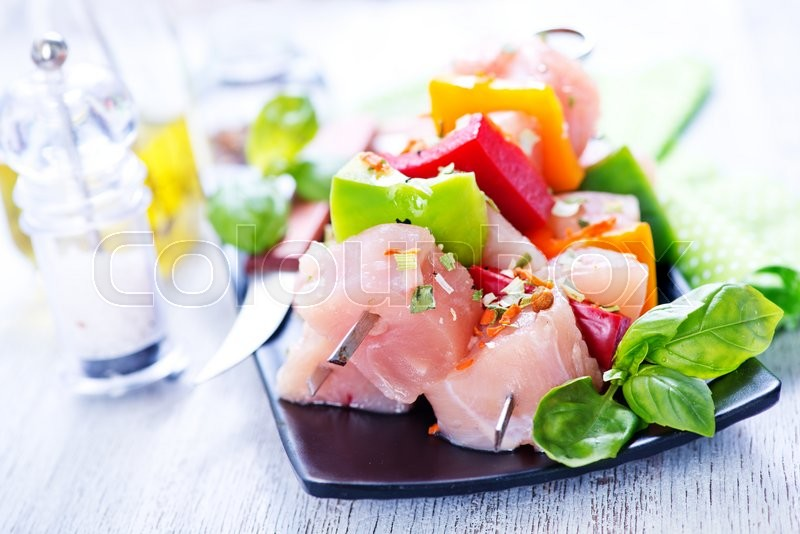 Stock image of 'raw chicken kebab on plate and on a table'