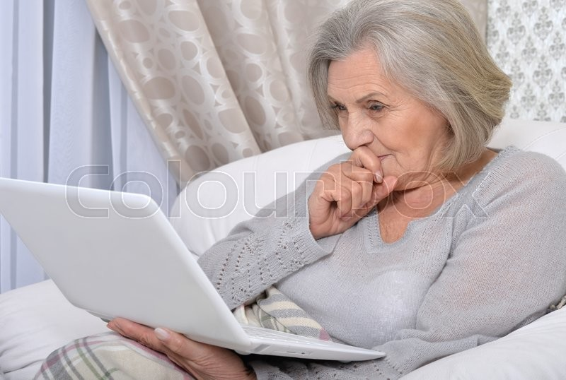 Stock image of 'Portrait of a joyful senior woman with laptop'