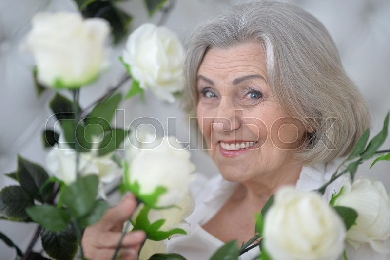 Stock image of 'Portrait of a senior woman portrait with blooming flowers'
