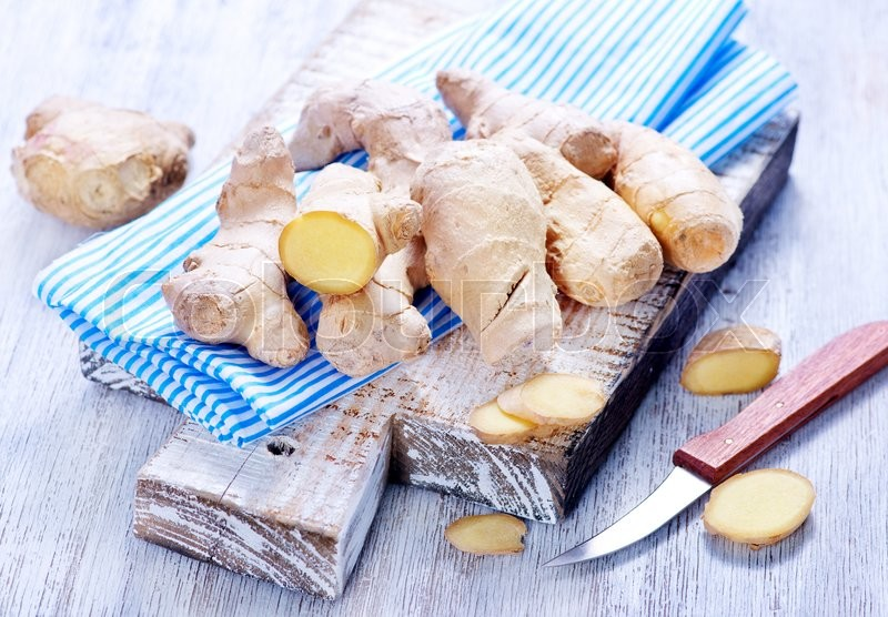 Stock image of 'fresh ginger on board and on a table'