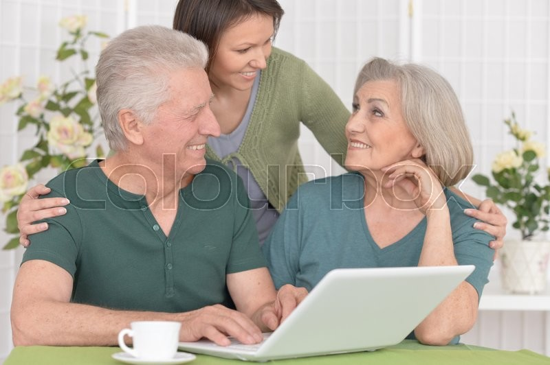 Stock image of 'Senior couple portrait with laptop with caring daughter'