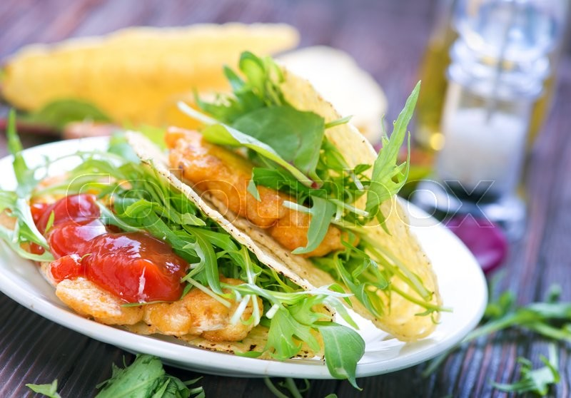 Stock image of 'taco with chicken and vegetables on a table'