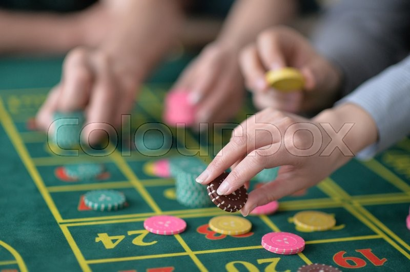 Stock image of 'human hands playing with  casino chips close up'