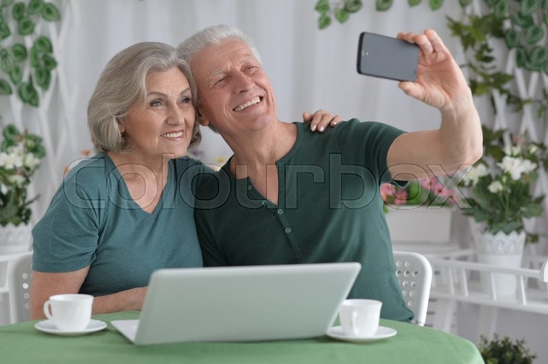 Stock image of 'Portrait of a senior couple taking selfie with phone'