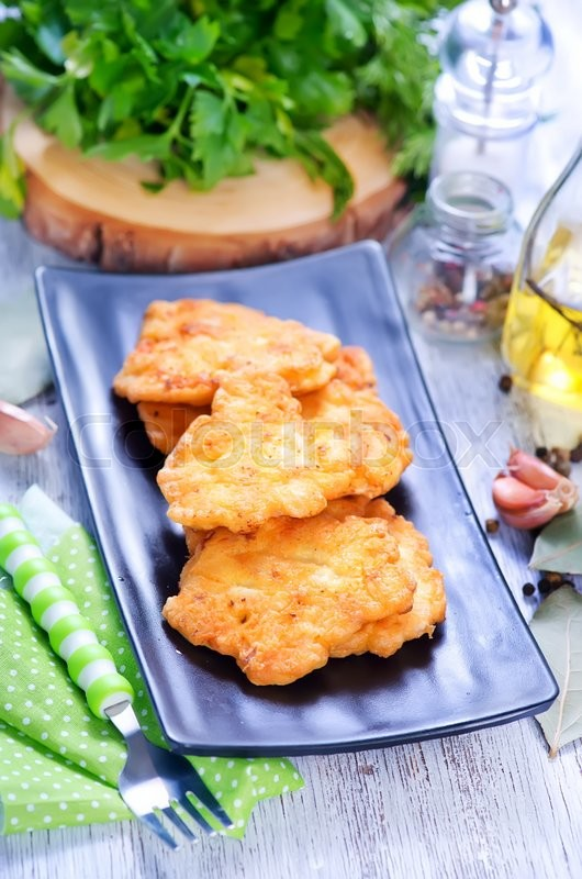 Stock image of 'fried chicken cutlets on plate and on a table'