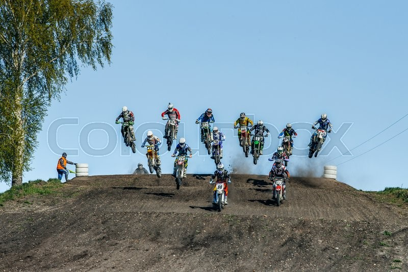 Editorial image of 'Miasskoe, Russia - May 02, 2016: large group of riders on motorcycles jumping over a mountain during Cup of Urals motocross'