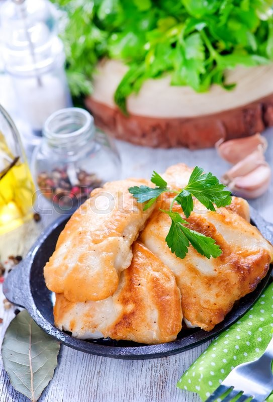 Stock image of 'fried fish on plate and on a table'