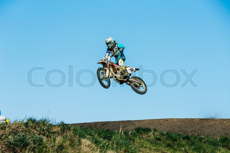 Editorial image of 'Miasskoe, Russia - May 02, 2016: racer motorcycle jump from mountain on a blue sky background during Cup of Urals motocross'