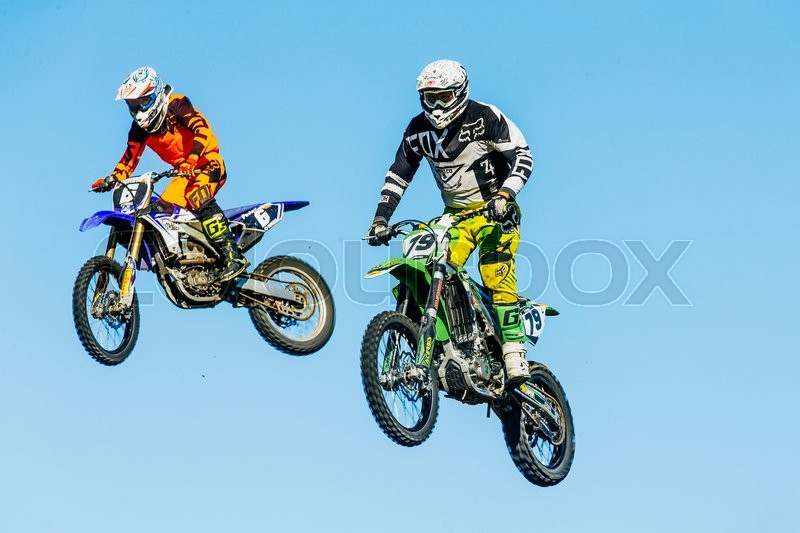 Editorial image of 'Miasskoe, Russia - May 02, 2016: closeup of two motorcyclists jump from a mountain on background of blue sky during Cup of Urals motocross'