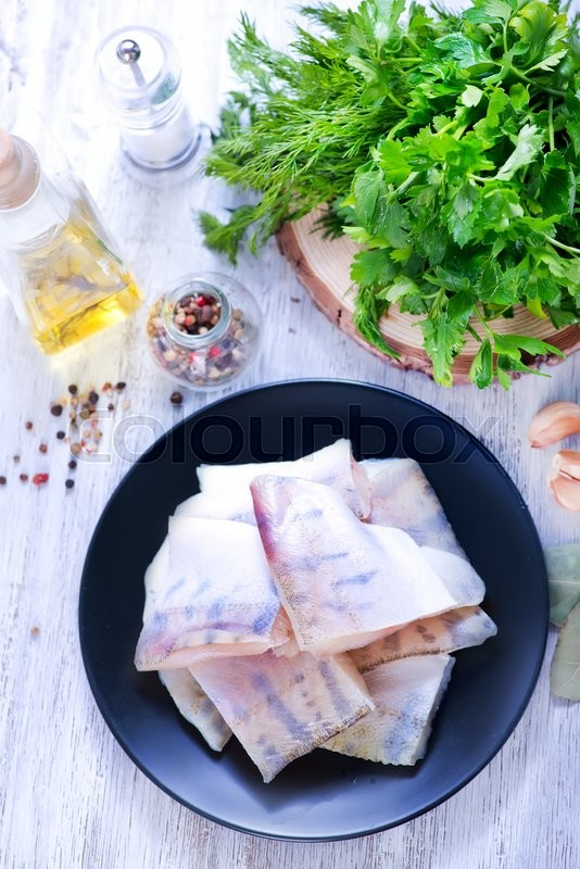 Stock image of 'raw fish fillet on plate and on a table'