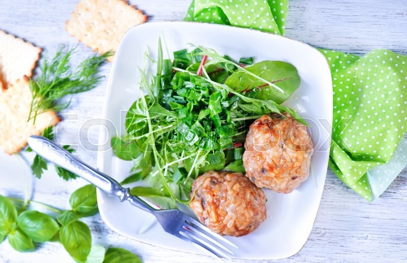 Stock image of 'cutlets with salad on plate and on a table'