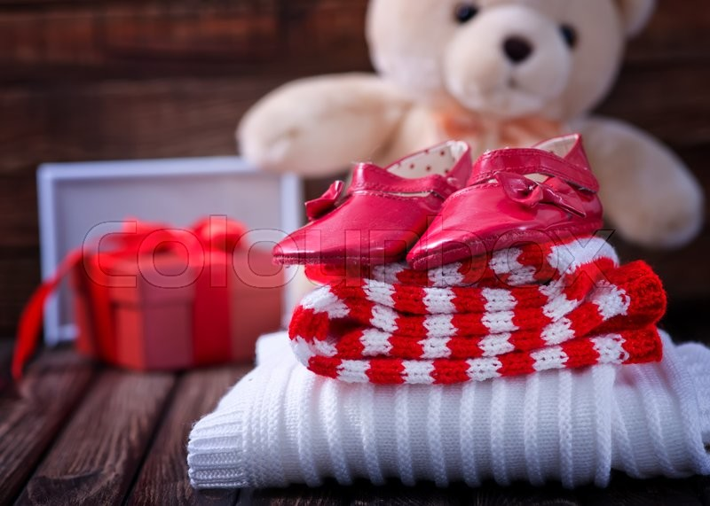 Stock image of 'baby clothes and shoes on the wooden table'