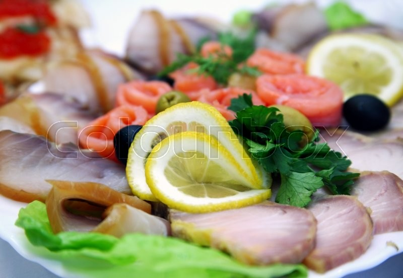 Stock image of 'Fish allsorts with a lemon and olives'
