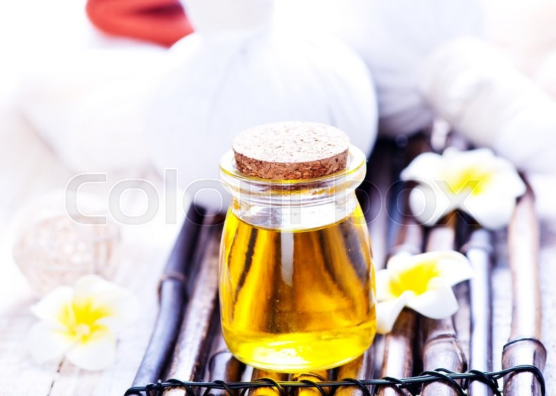 Stock image of 'oil for massag in glass bank and on a table'